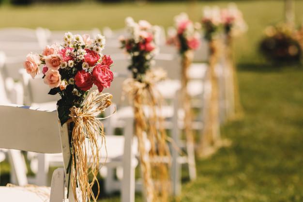 Cómo elegir las flores para tu boda - Ramos rosas en sillas blancas